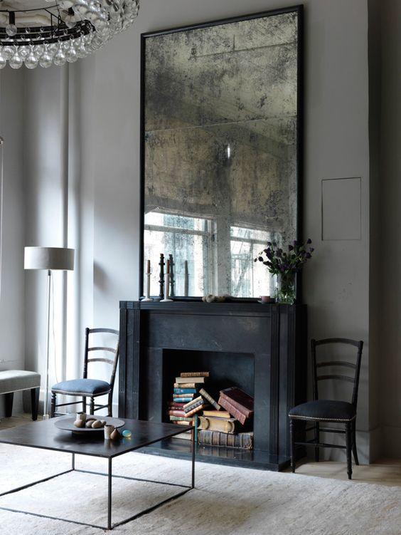 distressed mirror above fireplace bookshelf