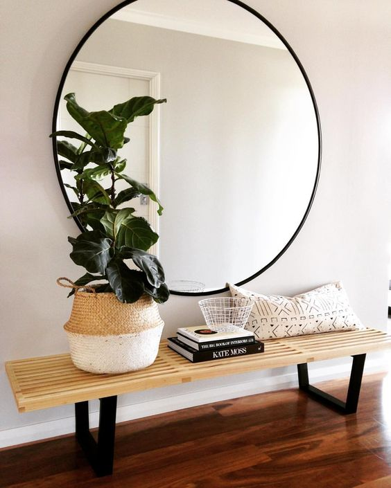 round mirror above bench with plant